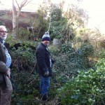 Two committee members infront of an overgrown fence, before work started to plant the area